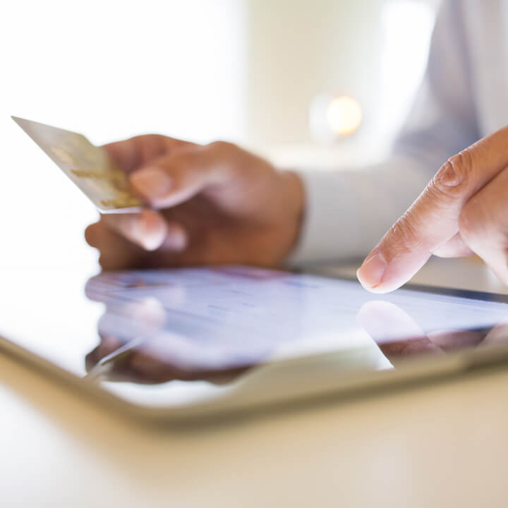 Man using tablet and holding credit card