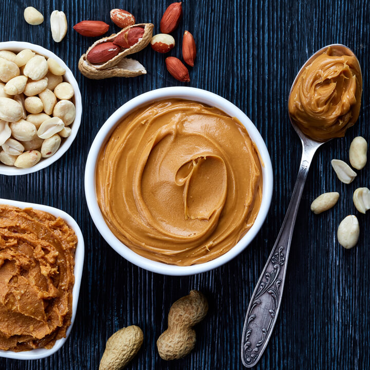 Two bowls of peanut butter and peanuts on dark wooden background