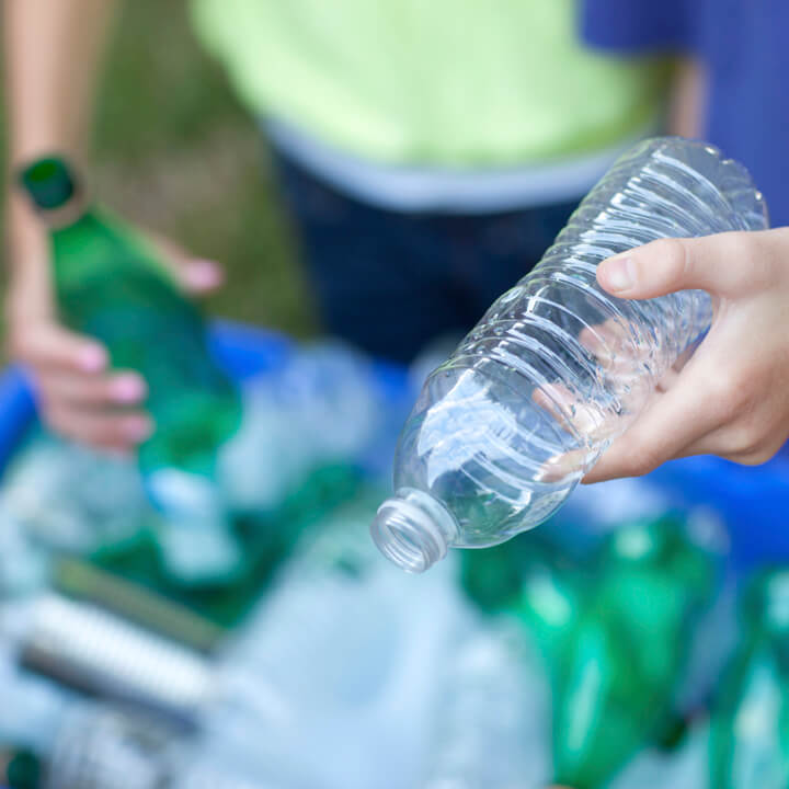 Hands placing bottles in recycling bin