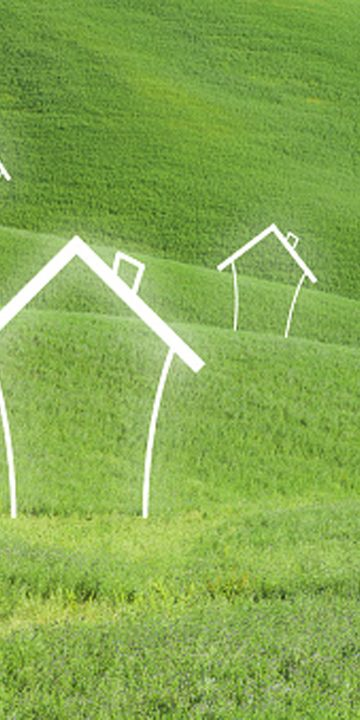 Abstract houses on green meadow landscape