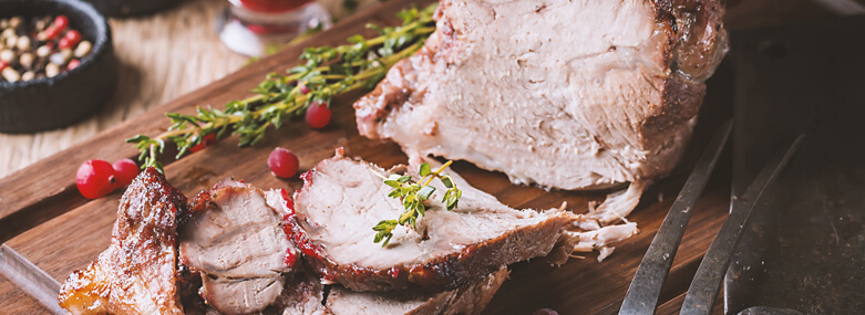 Cooked Pork with cranberry sauce and thyme over wooden background.