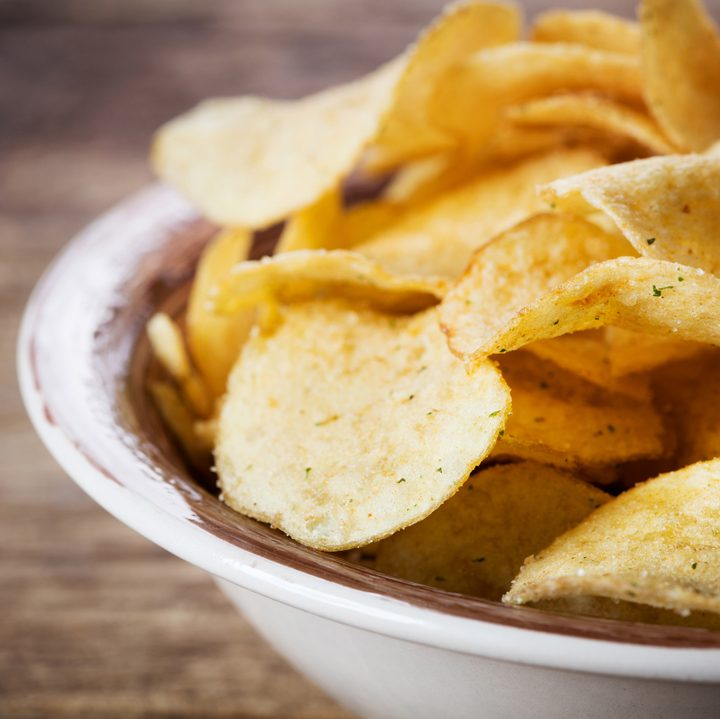 heap of potato chips in bowl on wooden background
