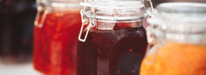 Glass jars with three types of Jam in them