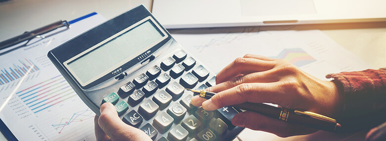 Businessman's hands with calculator and using laptop at the office and Financial data analyzing counting on wood desk