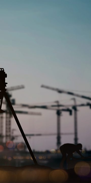 silhouette_engineer_looking_Loaders_and_trucks_in_a_building_site_over_Blurred_construction_worker_on_construction_site