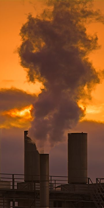 Chimney emitting air pollution and red sky