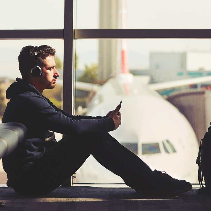 man_sat_at_airport_with_headphone_on