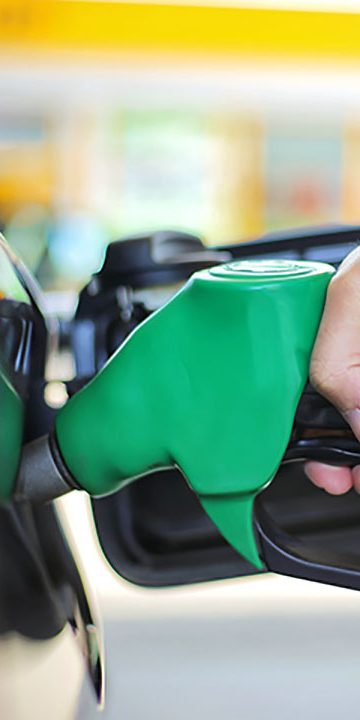 Close up hand holding fuel nozzle and being fill gas tank of black car