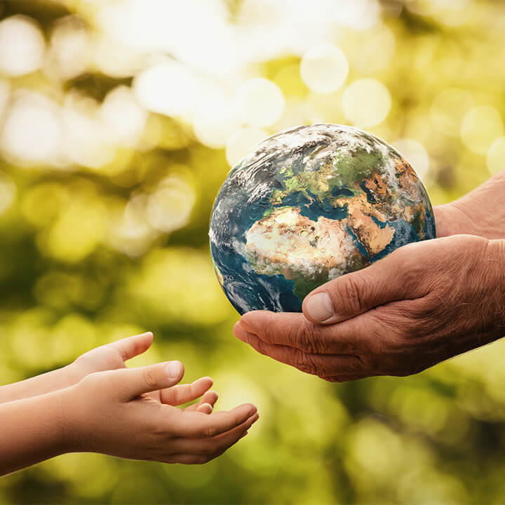 Senior_hands_giving_small_planet_earth_to_a_child