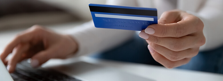 female_using_laptop_holding_credit_card_makes_payment