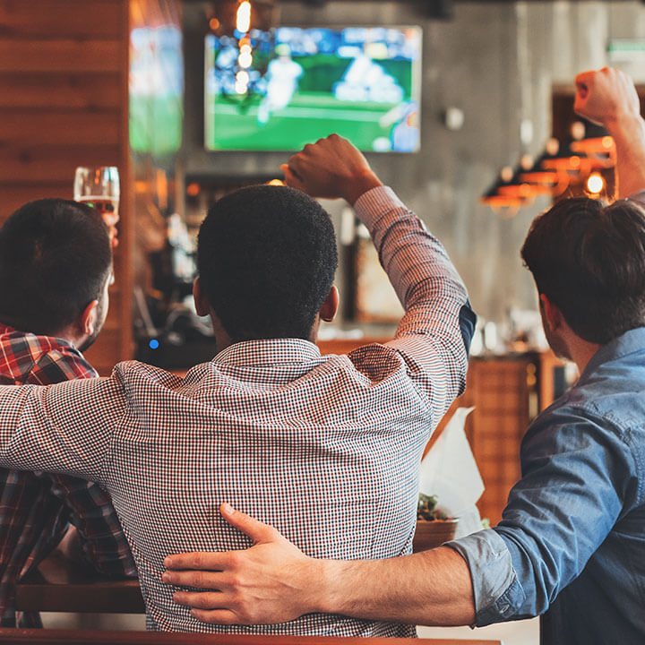 Three men watching football on TV in bar