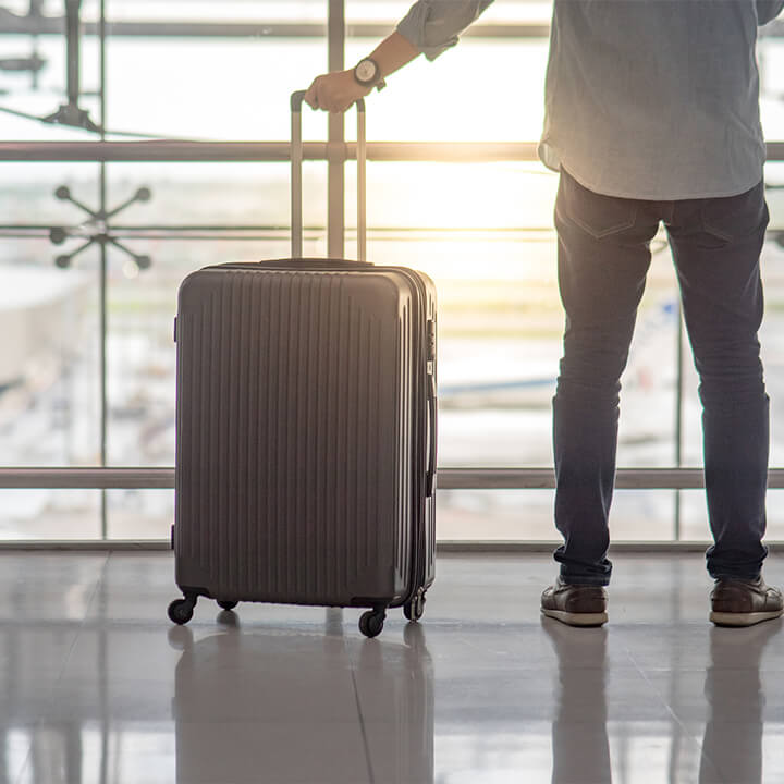 man_standing_in_airport_with_suitaacse