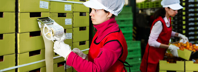worker_sticking_barcodes_on_boxes_of_fruit