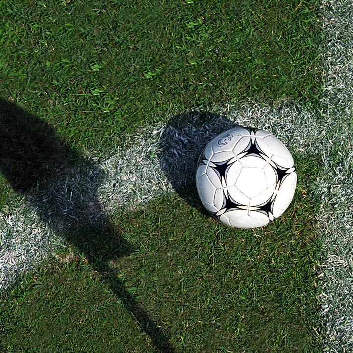 Football on grass by pitch marking and shadow of flag
