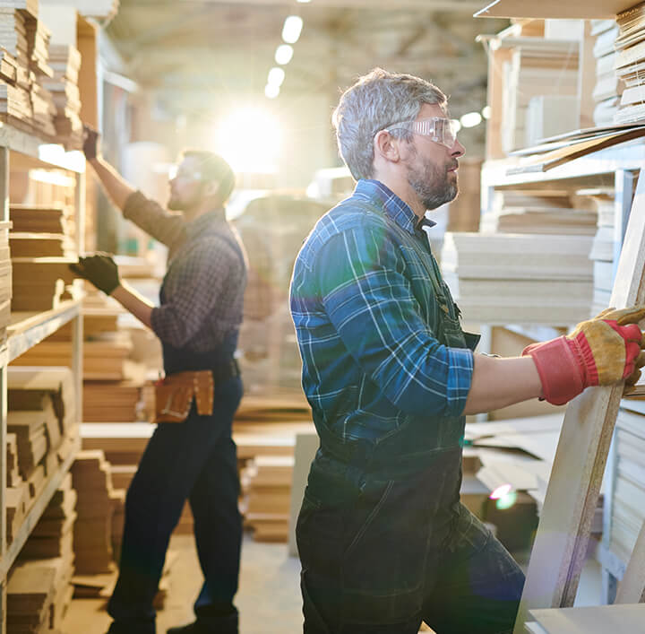 worker with beard wearing safety goggles and work gloves standing at shelves and checking wooden planks at warehouse