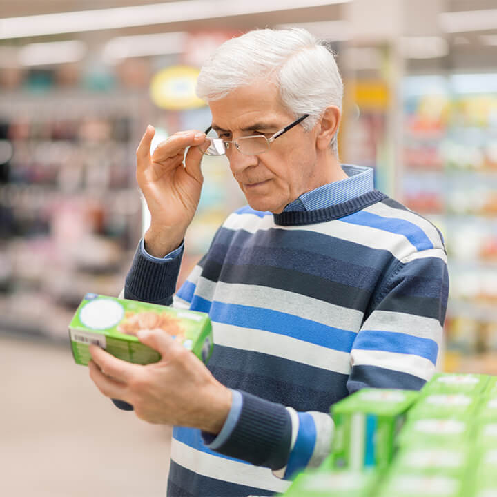 man_reading_food_label_at_a_grocery_store