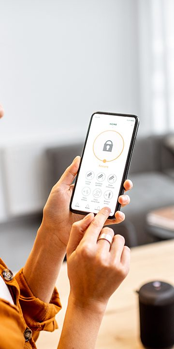 Woman managing home security from a mobile device