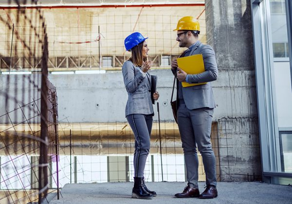 two-colleagues-with-helmets-on-heads-standing-in-building-in-construction