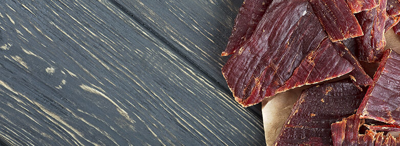 Spicy beef jerky on wooden background, top view.